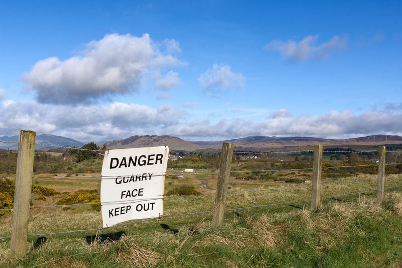 An old unused quarry along the West Highland Way Text Cloud - Sky Communication Sky Grass Day No People Outdoors Nature Quarry Construction Sign Danger Danger Sign Disused Quarry Landscape Rural Scene West Highland Way Highlands Picturesque Rural Scenes Hiking Trekking Scotland Peaceful