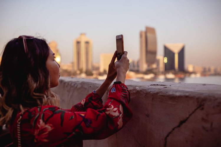 Woman photographing with smart phone in city