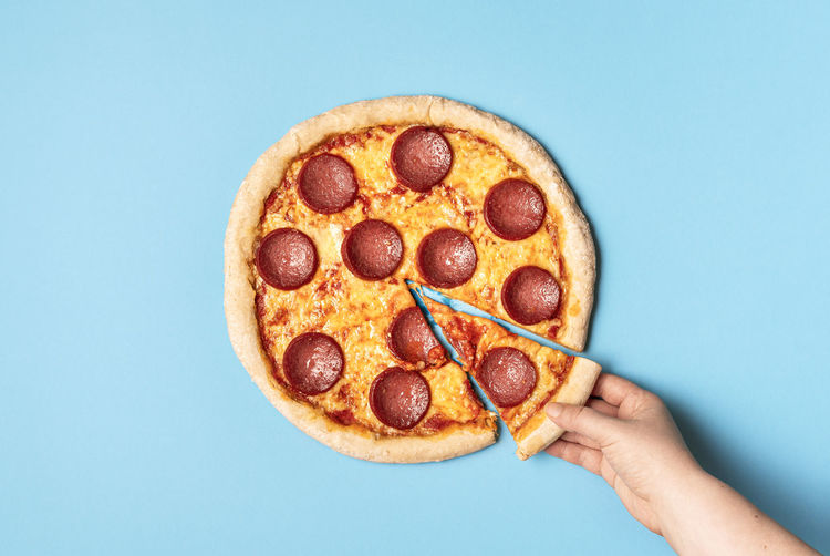 Close-up of hand holding pizza over white background