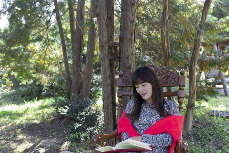 Portrait of woman sitting on tree trunk in forest