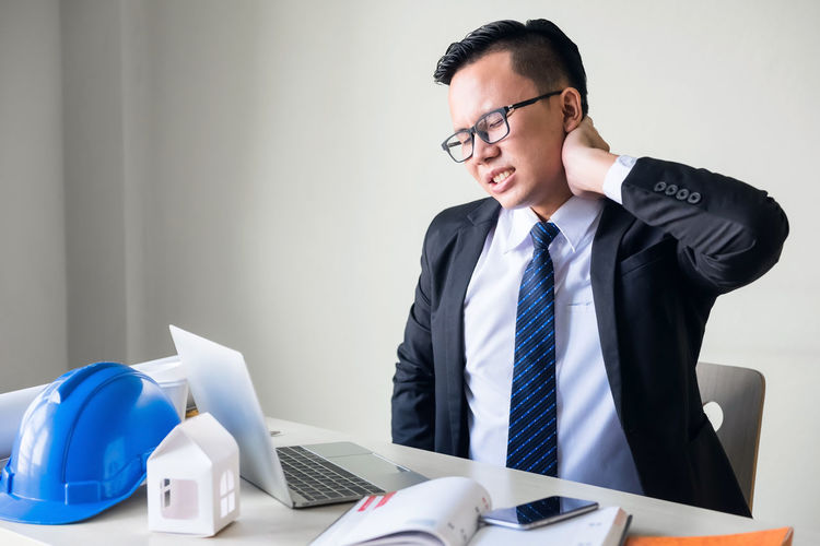 Businessman With Neckache Sitting At Desk In Office