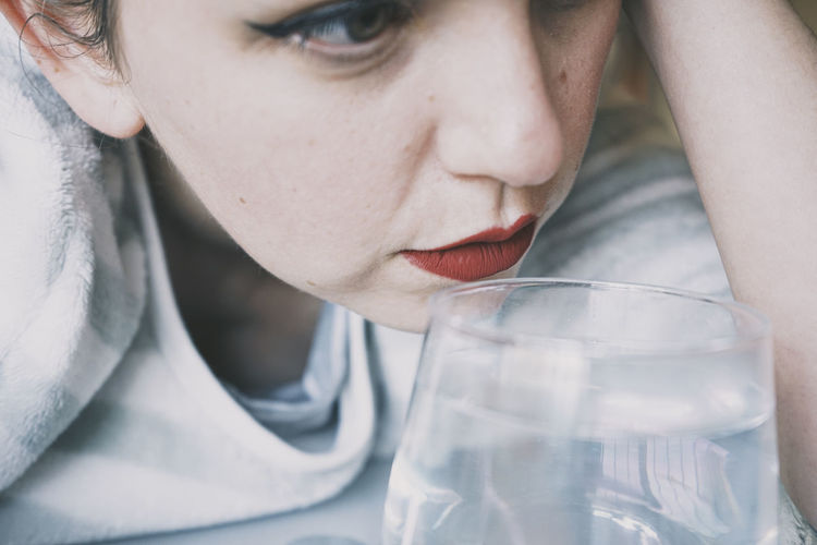 Close-up portrait of young woman drinking glass