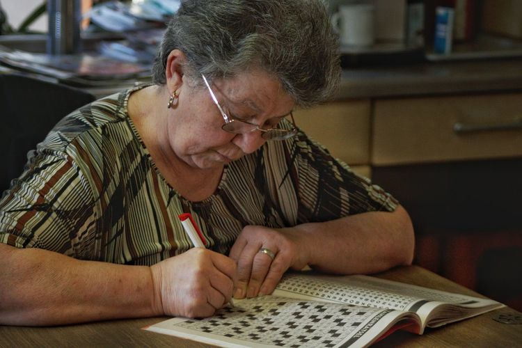 Woman writing on book at home