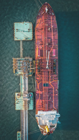 Aerial view of cargo ship moored by offshore platform