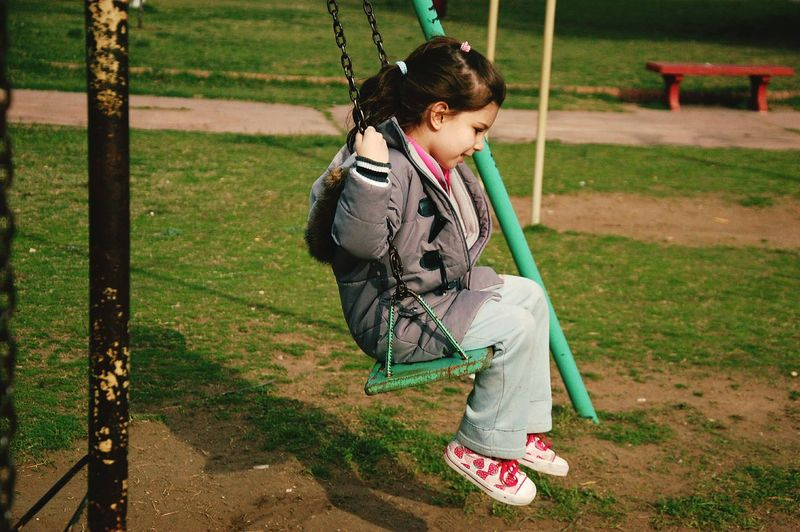 Side view of cute girl swinging in park