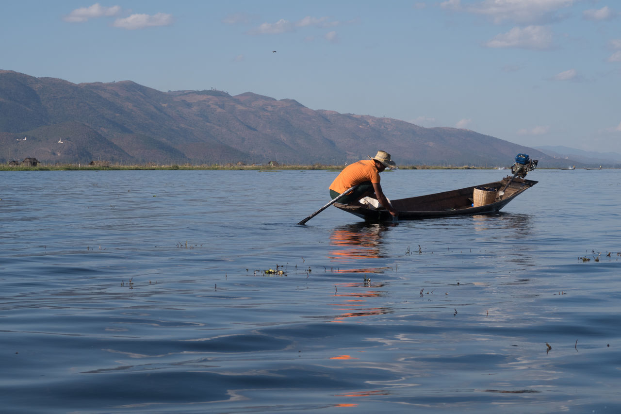 water, nature, waterfront, transportation, beauty in nature, real people, scenics, men, outdoors, one person, sky, day, nautical vessel, occupation, oar, mountain, people