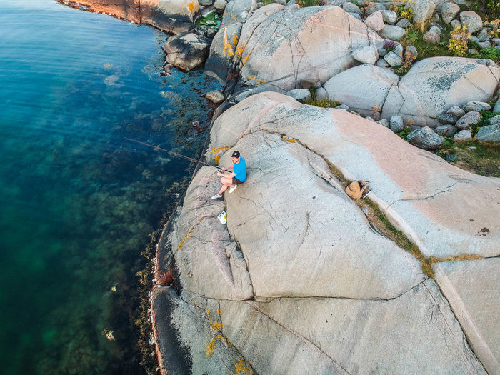 High angle view of man on rock by sea