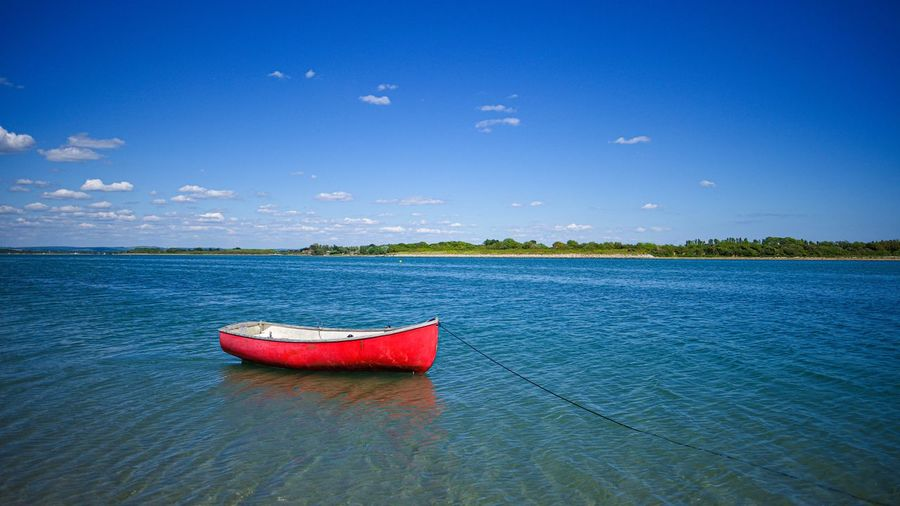 Water Sky Blue Beauty In Nature Scenics - Nature Tranquility Nautical Vessel No People Nature Tranquil Scene Day Transportation Sea Outdoors Horizon Red Horizon Over Water Idyllic Floating On Water Rowboat