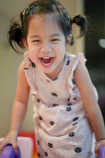 Cheerful girl playing at home
