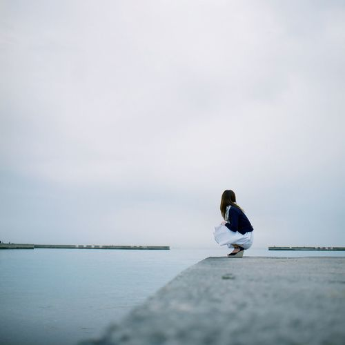 Side View Of Woman Crouching On Pier Over Lake Against Sky