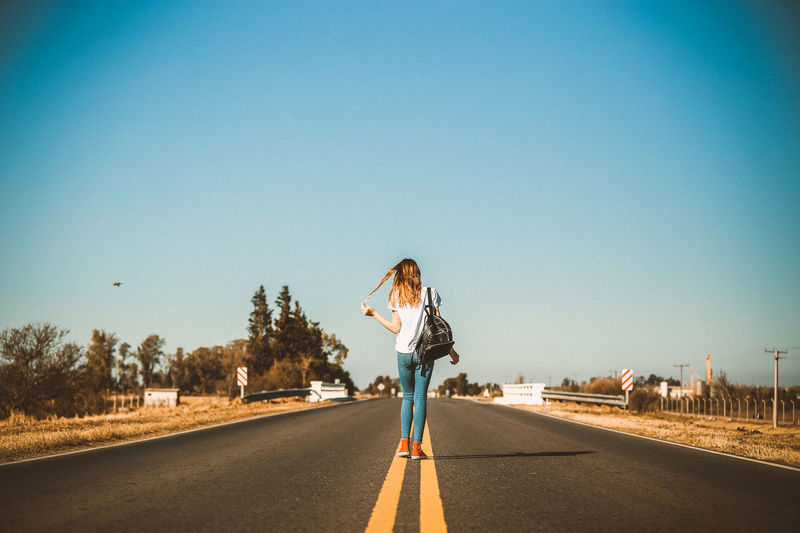 Rear View Of Woman Standing On Road Against Clear Blue Sky