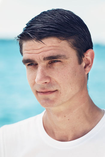 Close-up of man looking away against sea
