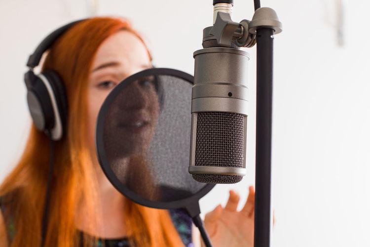 Close-up of singer singing song at studio