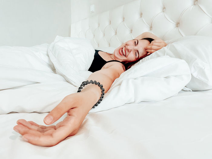 Midsection of woman sleeping on bed