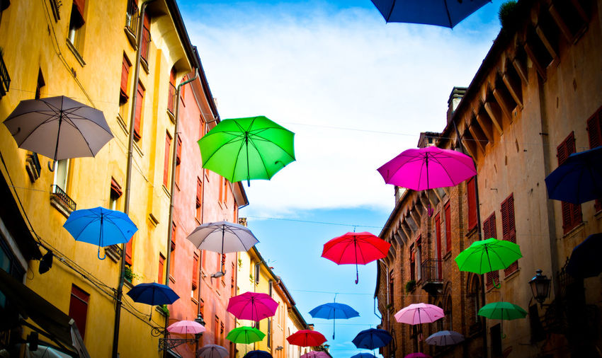 Colorful umbrellas hanging on amidst buildings