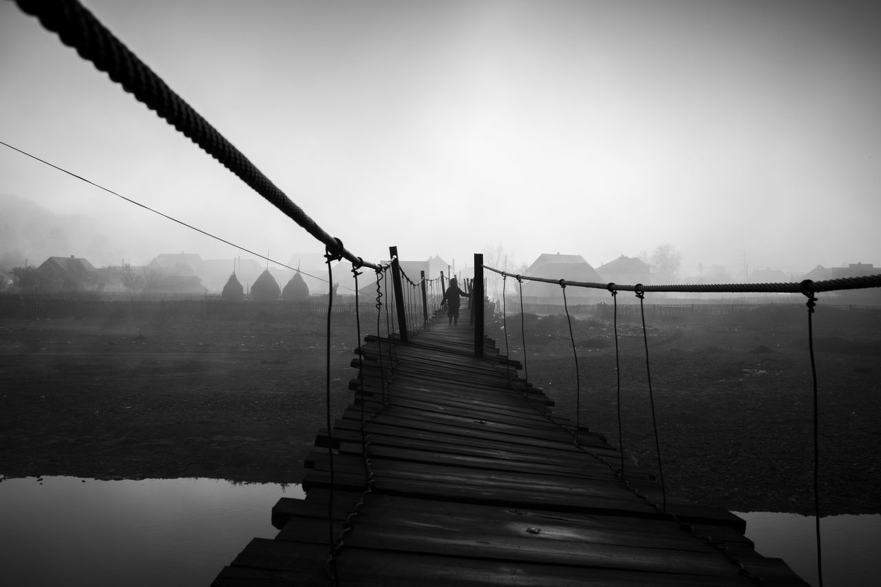 Fence By Bridge Against Sky