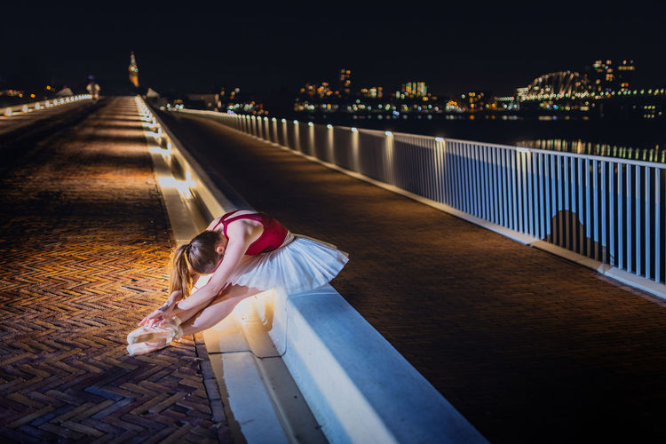 Ballerina sitting by street at night