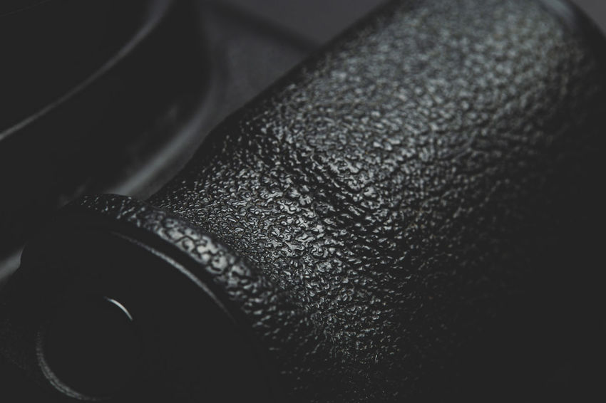 close up view of a DSLR camera grip in dark atmosphere Indoors  Close-up No People Black Color Single Object High Angle View Still Life Technology Selective Focus Photography Themes Dark Focus On Foreground Leather Equipment Fashion Metal Security Extreme Close-up Shape Camera Grip Photography DSLR Videography Alloy