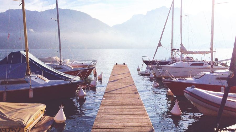 Boats moored by pier on lake annecy at morning