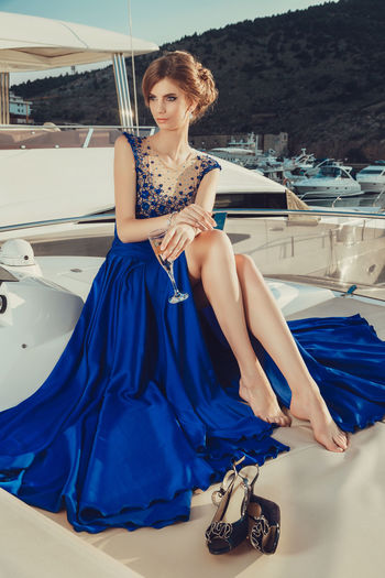 Beautiful young perfect girl in a dress and makeup, summer trip on a yacht with white sails on