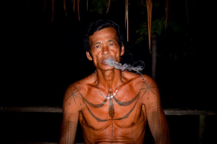 Portrait of shirtless man with tattoo smoking at night