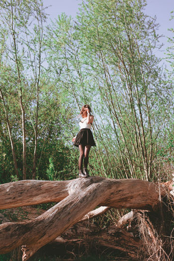 Full length of young woman standing on fallen tree at forest