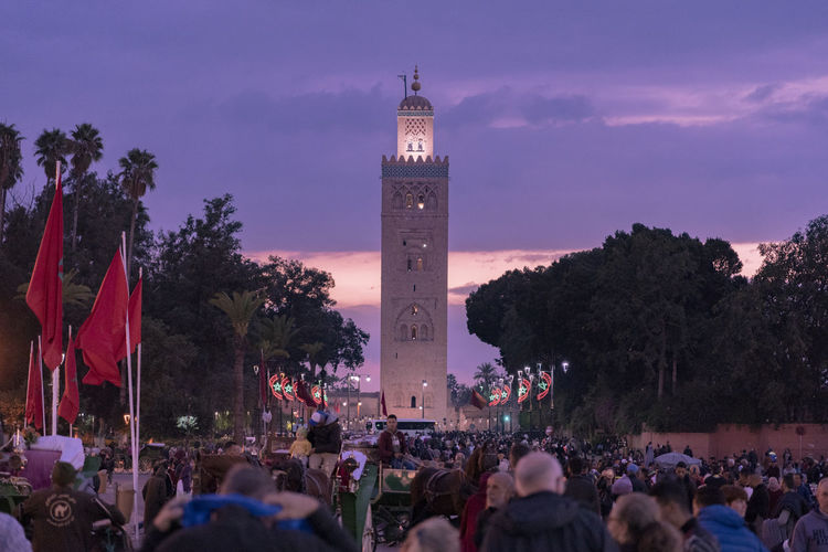 Crowd Architecture Tower Building Exterior Sky Dusk Travel Destinations History City Illuminated Place Of Worship Mosque Middle East North Africa Purple Sky Avenue Walkway Mall Pedestrian Walkway Marrakech Palm Trees Large Group Of People Building Group Of People