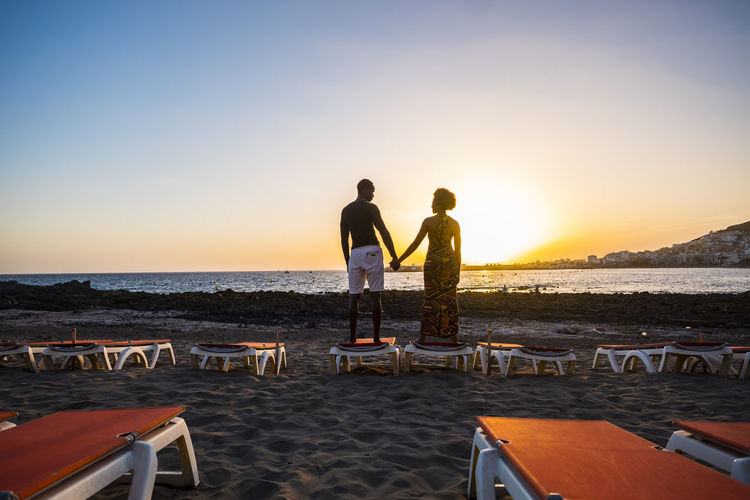 Rear view of man holding hands of woman while standing on sand against sea during sunset