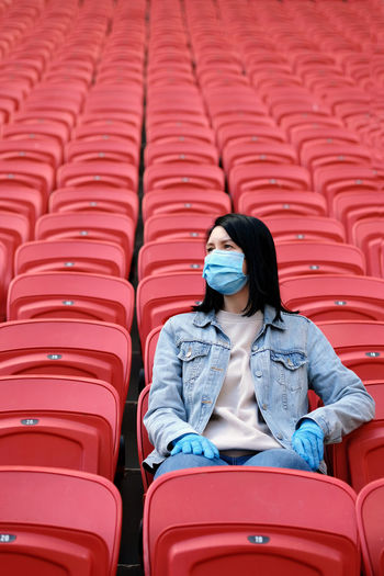 A female fan in a medical mask and rubber gloves sits alone in an empty stadium with red seats.