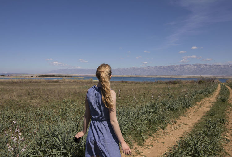Blond Hair Blonde Girl Blue Day Field Grass Grass Landscape Nature One Person Outdoors Path In Nature Path To Nowhere Pathway Plant Rear View Scenics Sea And Sky Seascape Sky Standing Tranquil Scene Tranquility Walking Wind