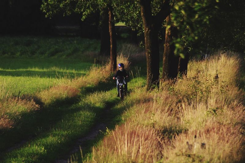 Man Riding Motorcycle Amidst Grass