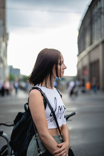 Young woman looking away while standing on city street against sky