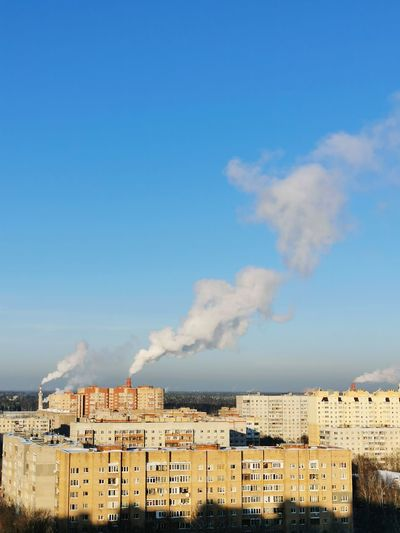 Smoke emitting from factory against blue sky