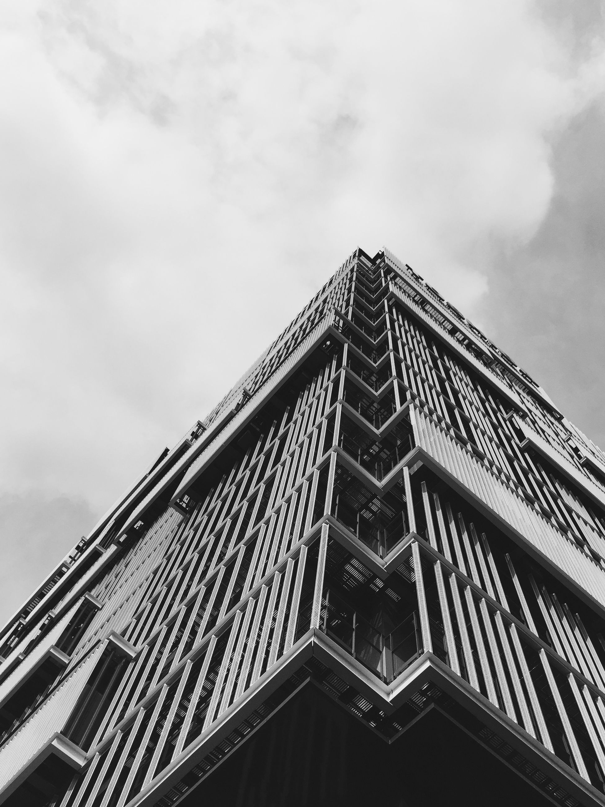 architecture, low angle view, built structure, building exterior, sky, cloud - sky, architectural feature, city, tower, tall - high, pattern, day, modern, cloud, building, outdoors, cloudy, no people, window, office building