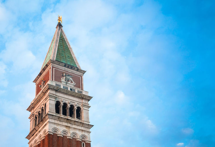 Low angle view of san marco campanile against cloudy sky