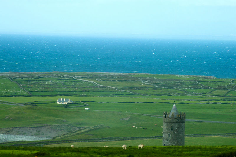 Panoramic view of wide green pasture lands at the edge of the sea