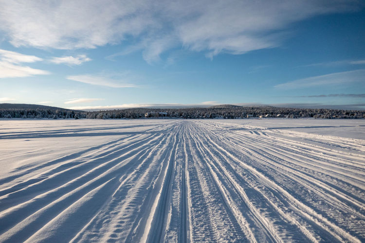 Tire tracks on snow covered land