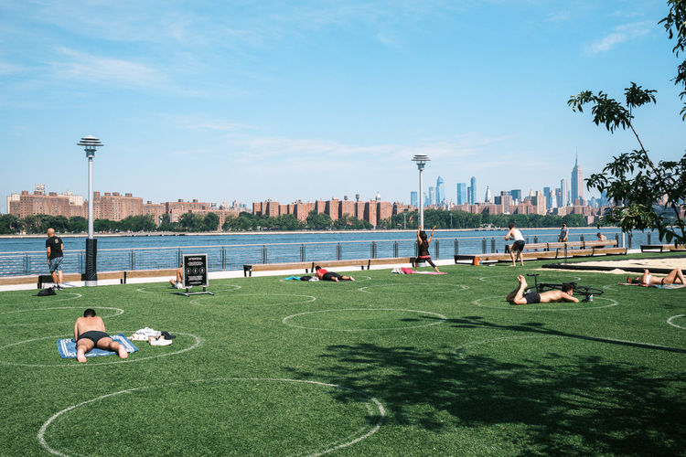 People relaxing on grass in city against sky
