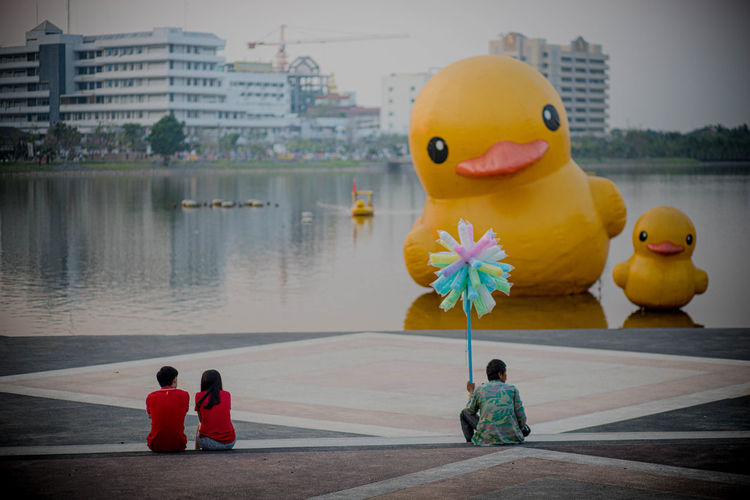 Rear view of people with toy sitting by lake