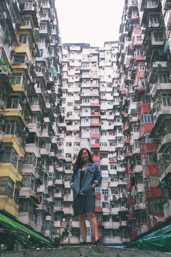 Full length of woman standing against buildings in city