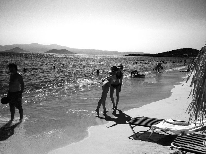 Two friends enjoy a sunset on the beach at Naxos, Greece. Beach Holidays Horizontal Naxos Naxos Beach Naxos Greece Naxos_island Real People Sand Summer Fun Summer Holidays Sunset Sunset On The Beach Sunshine Two People Vacations Water