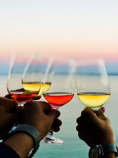 Close-Up Of Hands Holding Wine Glasses Against Sky During Sunset