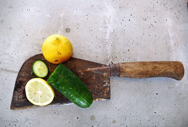Directly Above Shot Of Lemons And Cucumber On Rusty Axe