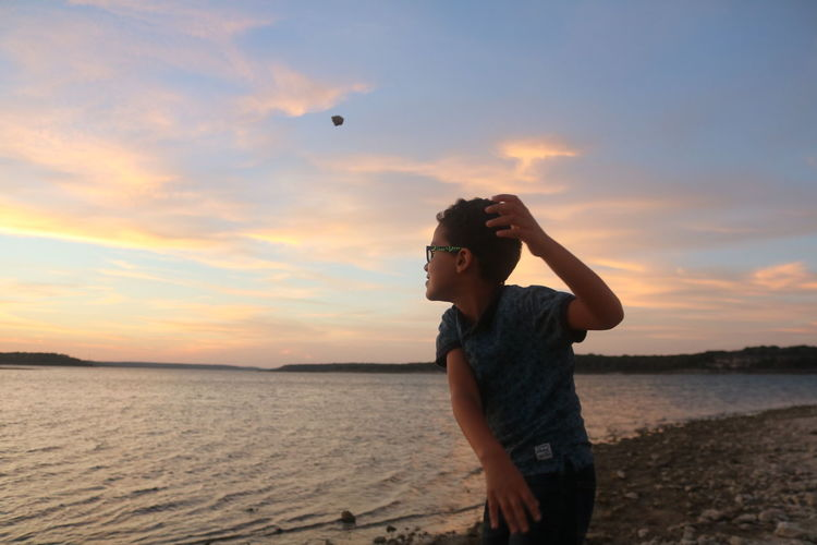 Boy Throwing Rock In Lake Against Sky During Sunset