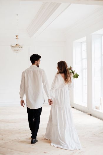 Rear View Of Couple Holding Hands While Walking In Room During Wedding Ceremony