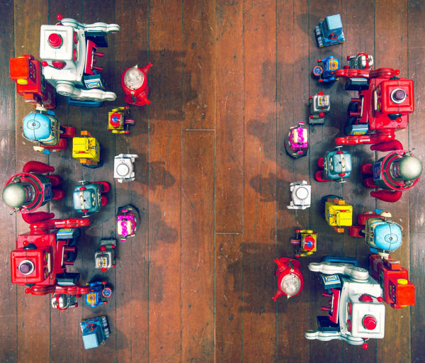 robot wars ! Face Off Above Close-up Collection Conceptual Conflict Creativity Fighting Large Group Of Objects Lots Multi Colored No People Oppisite Oppisite Sides Oppisition Retro Styled Robot Army Toy Toy Robots Two Sides War Wood - Material Wooden Flooring