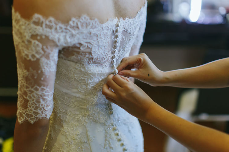 Cropped hands of woman buttoning bride dress