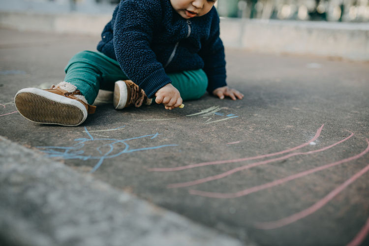 Low section of boy drawing on floor