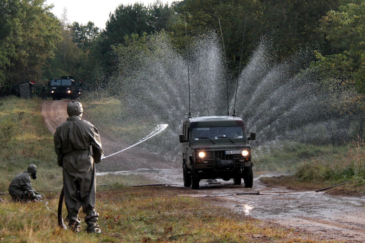 spraying, water, transportation, two people, land vehicle, working, tree, real people, outdoors, motion, firefighter, men, day, occupation, nature, adult, people