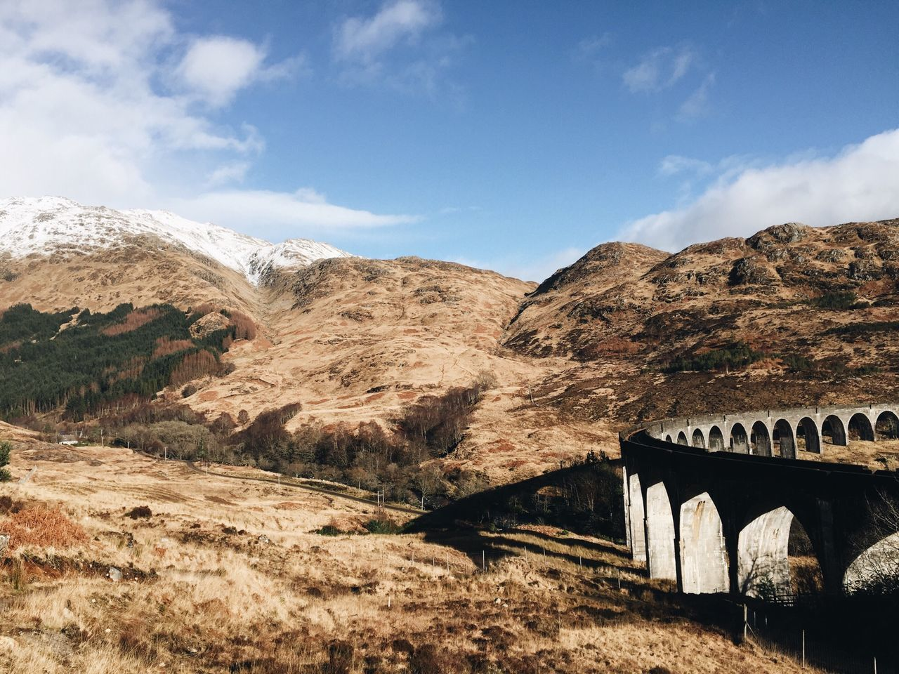 Glenfinnan viaduct by mountains against sky